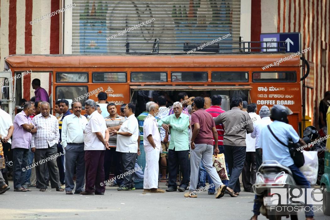 Stock Photo: Bangalore, India - October 23, 2016: Large group of people buying hot coffee from a mobile canteen while other stand aside in the Avenue road.