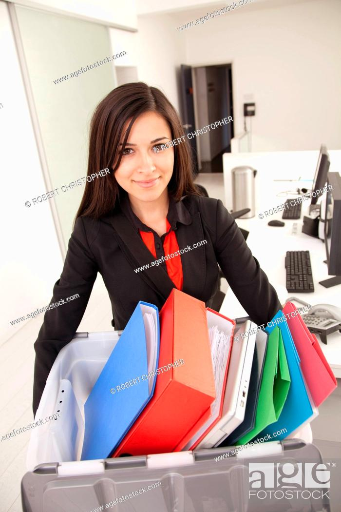 Stock Photo: Businesswoman carrying box of binders.