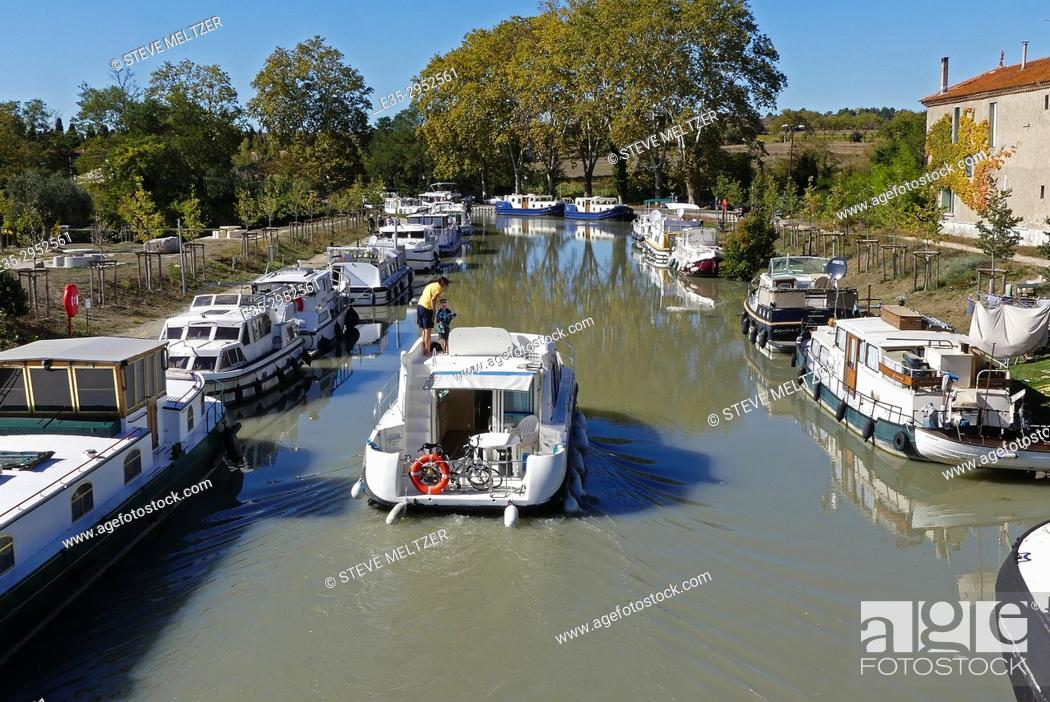 Stock Photo: A father and son piloting a boat down the Canal du Midi at Capestang, France.