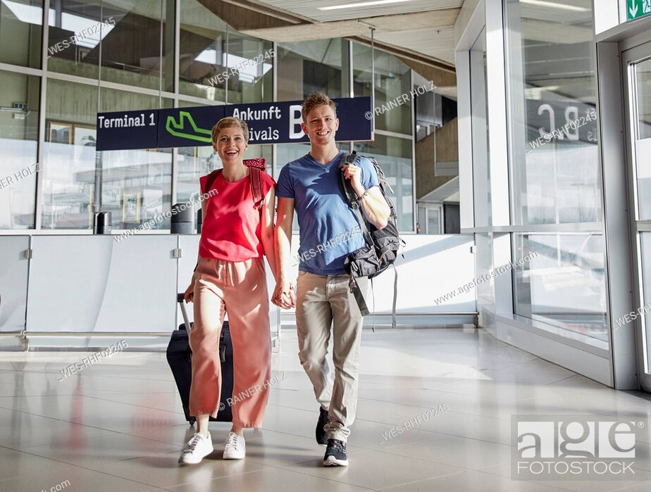Stock Photo: Happy couple walking hand in hand at the airport.