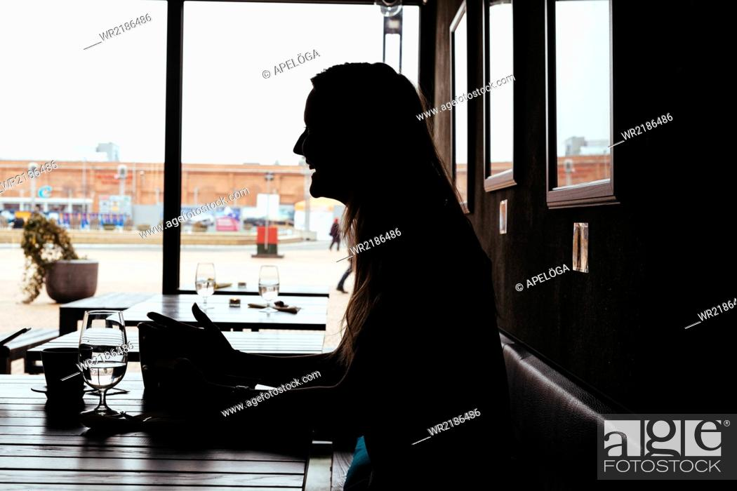 Stock Photo: Side view of silhouette female customer sitting in cafe.