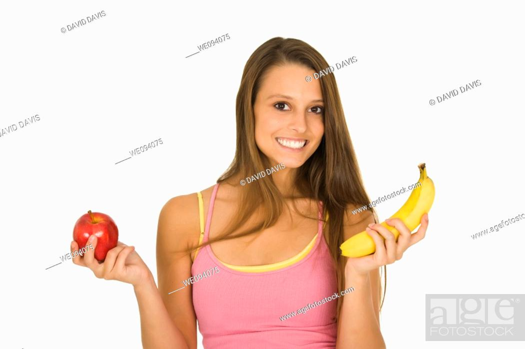 Stock Photo: Caucasian woman holding an apple and a banana trying to decide which one to eat.