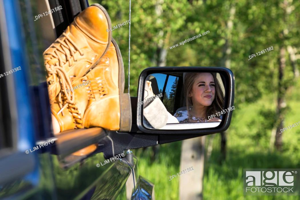 Stock Photo: A female passenger with her feet out the window of the vehicle during a rest stop on a road trip; Edmonton, Alberta, Canada.