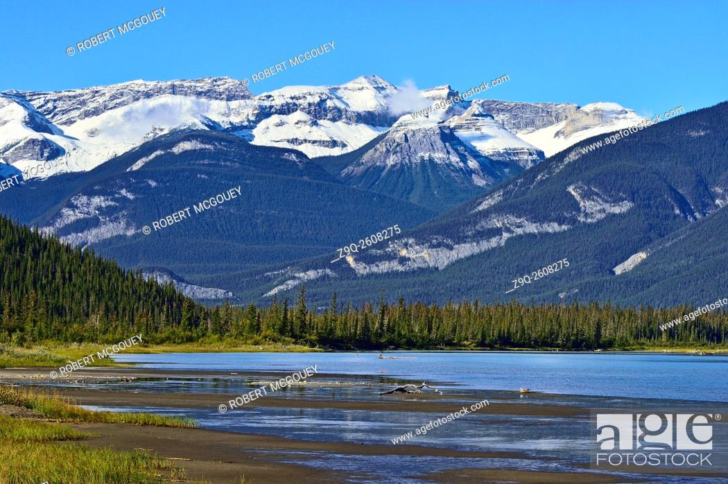 Stock Photo: A late summer landscape image looking to the west end of Jasper Lake with snow-capped rocky mountains of Jasper National Park in the background.