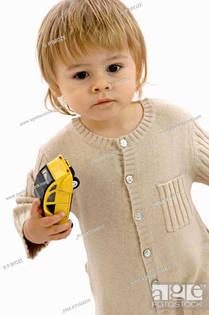 Stock Photo: Portrait of a baby boy holding a toy car.