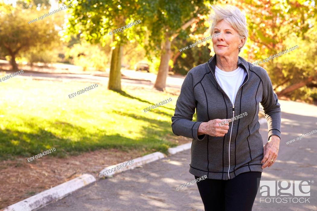 Stock Photo: Front View Of Senior Woman Jogging Through Park.