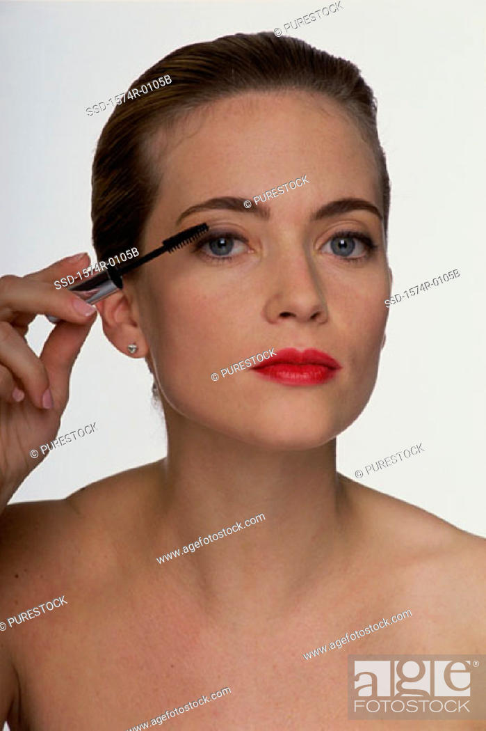 Stock Photo: Portrait of a young woman applying mascara.