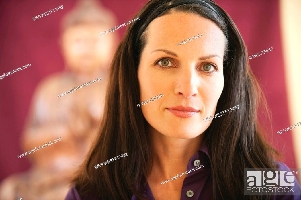Stock Photo: Portrait of a woman, buddha statue in background, close-up.