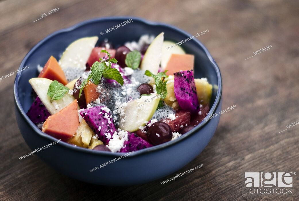 Stock Photo: exotic mixed tropical asian fruit salad with basil seeds and coconut in bowl outdoors.