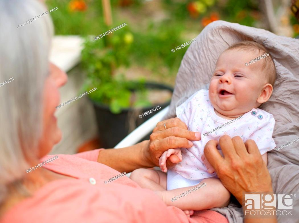 Stock Photo: Germany, Bavaria, Woman with grandchild sitting in lawn chair, smiling.