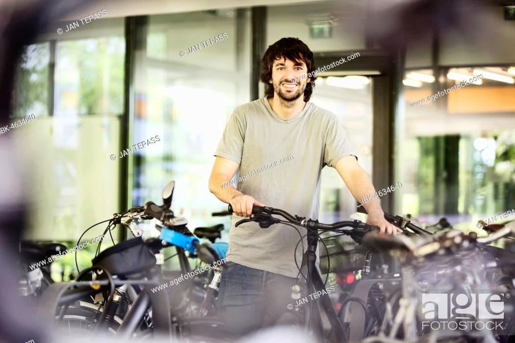 Stock Photo: Young man, student, parks his bicycle, University, Aachen, North Rhine-Westphalia, Germany.