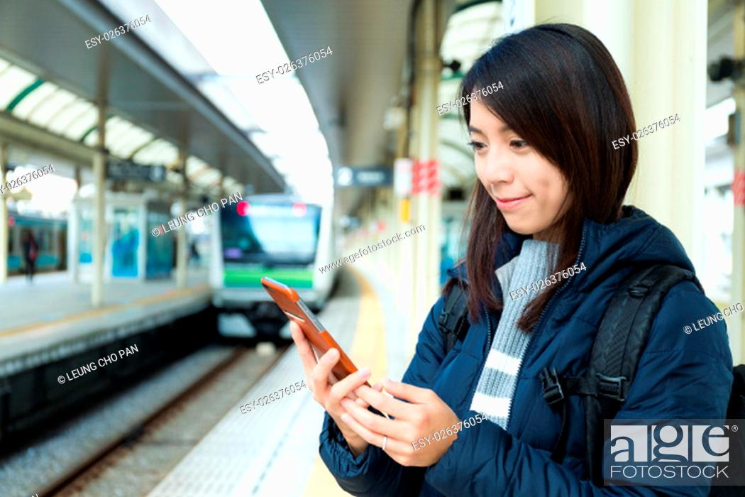 Stock Photo: Woman use of mobile phone in trains station.