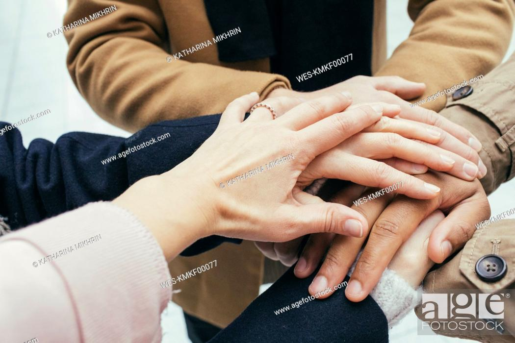 Stock Photo: Group of friends putting hands together.
