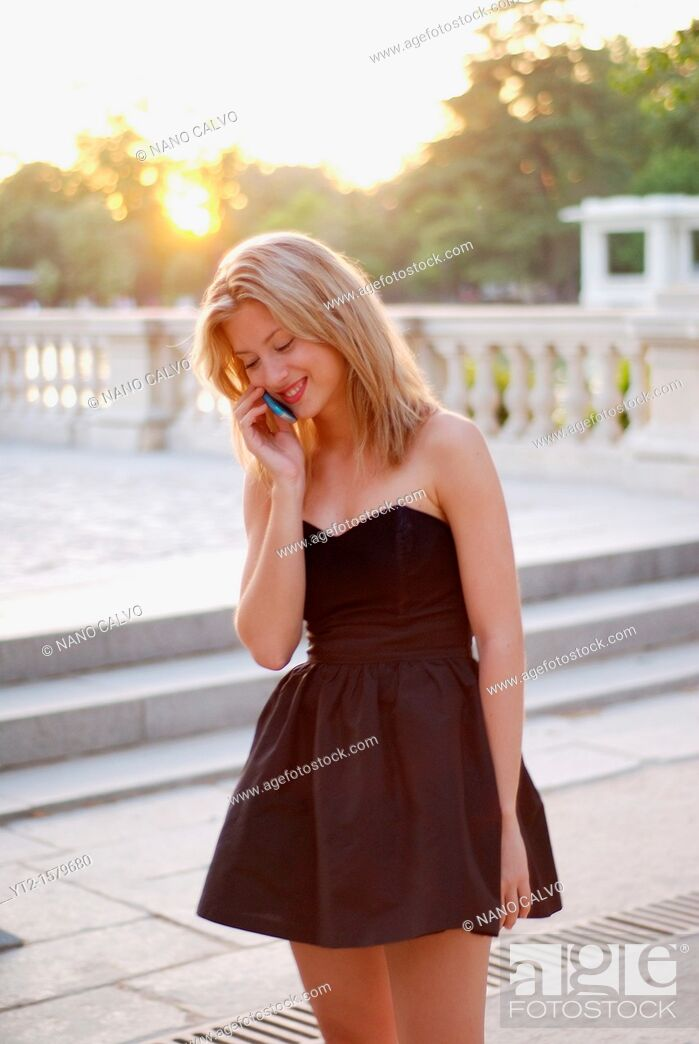 Stock Photo: Cute young blonde woman in a black elegant dress talking on her phone.