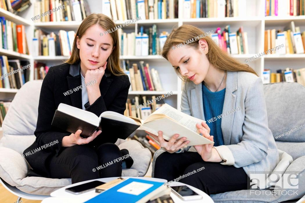 Stock Photo: Two teenage girls sitting in a public library reading books.