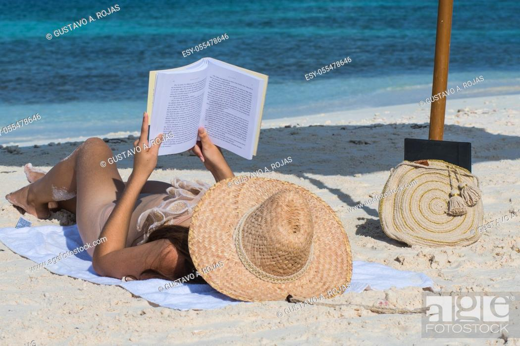 Stock Photo: Portrait of a young woman relaxing on the beach, reading a book.