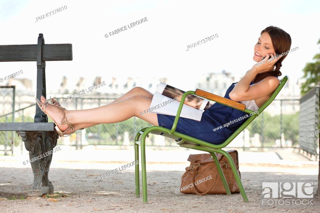 Stock Photo: Woman reclining in a chair and talking on a mobile phone, Jardin des Tuileries, Paris, Ile-de-France, France.