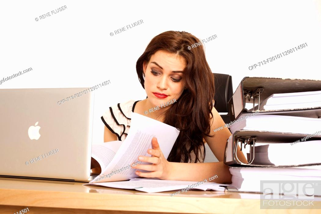 Imagen: A beautiful young woman, lady, girl, secretary, personal assistant, office work, job, employee, worker, computer, notebook, MacBook Pro, paper work, folders.
