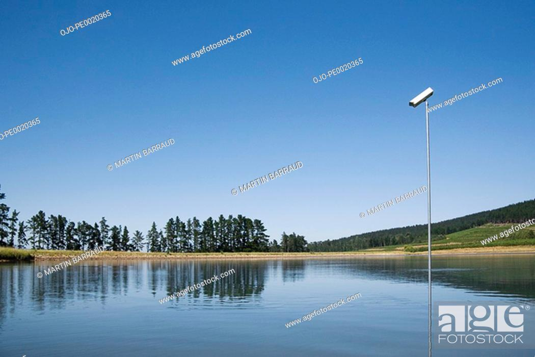 Stock Photo: Surveillance camera in water with trees.