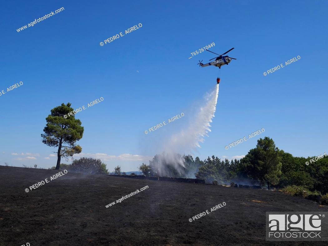 Imagen: A helicopter with a bag of water cools one of the areas affected by fire in the province of Lugo, Galicia, Spain.