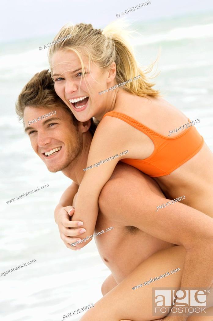 Stock Photo: Man giving woman piggyback ride on the beach.
