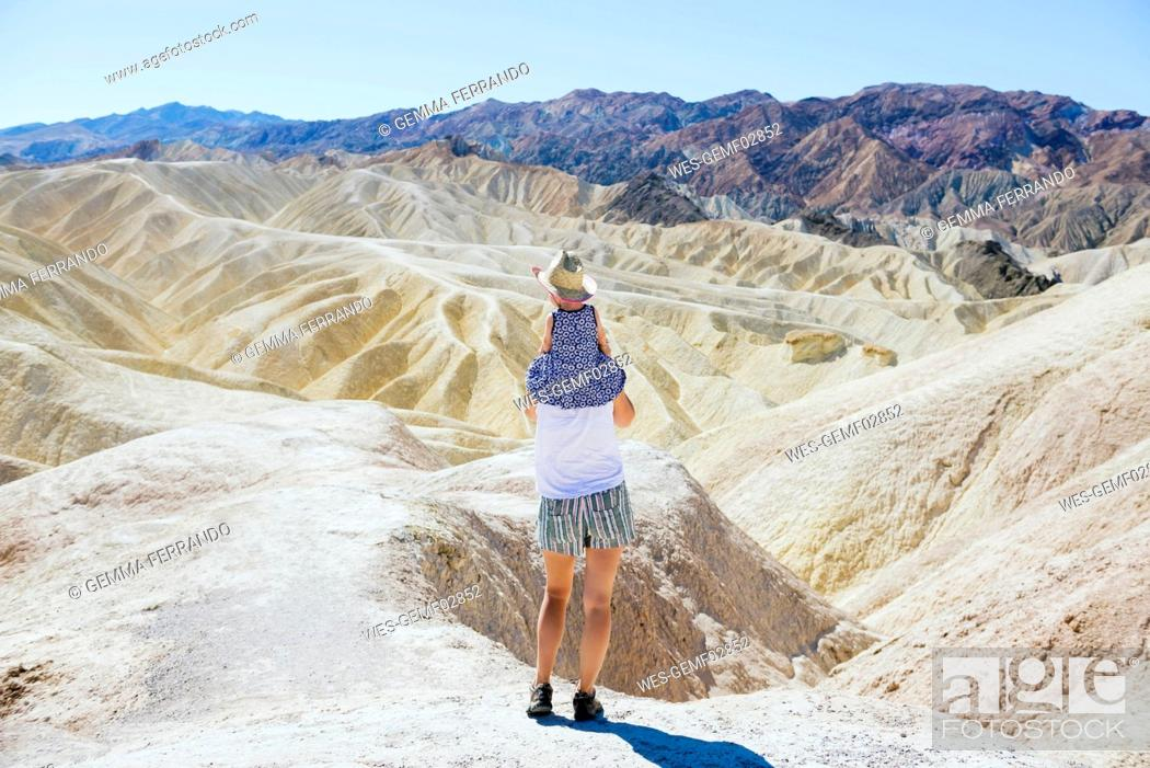 Stock Photo: USA, California, Death Valley National Park, Twenty Mule Team Canyon, back view mother carrying baby girl.