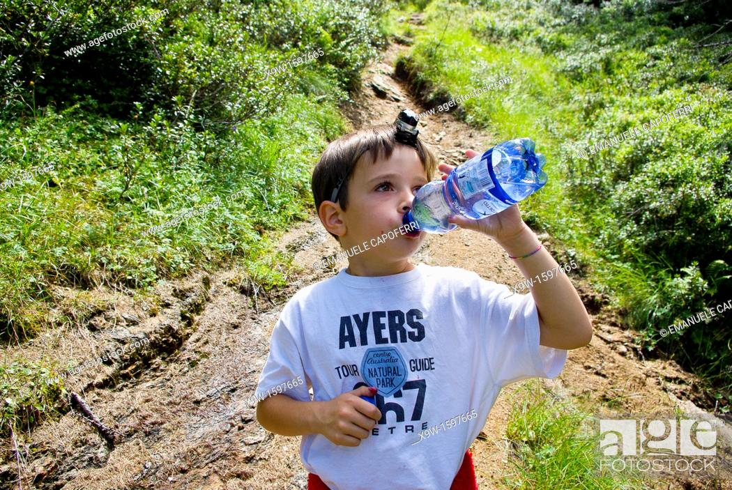 Stock Photo: children drink water in the natural scene.