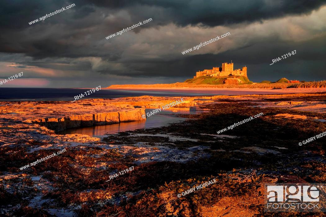 Stock Photo: A storm passes behind Bamburgh Castle with the last light of the day illuminating the rocky shoreline and castle, Northumberland, England, United Kingdom.