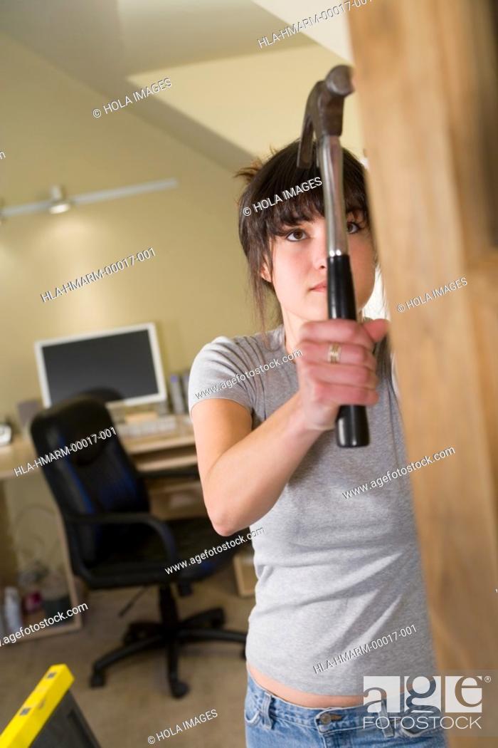 Imagen: Woman hammering in home office.