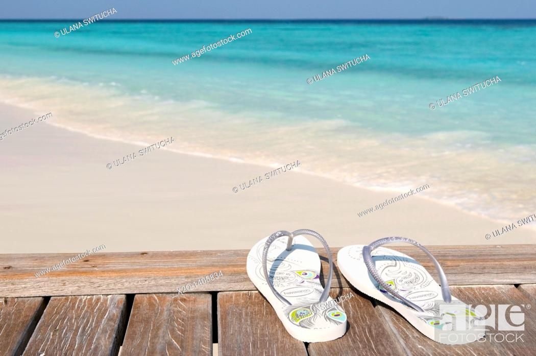 Stock Photo: Flip flops on a jetty next to a white sand beach Maldives.
