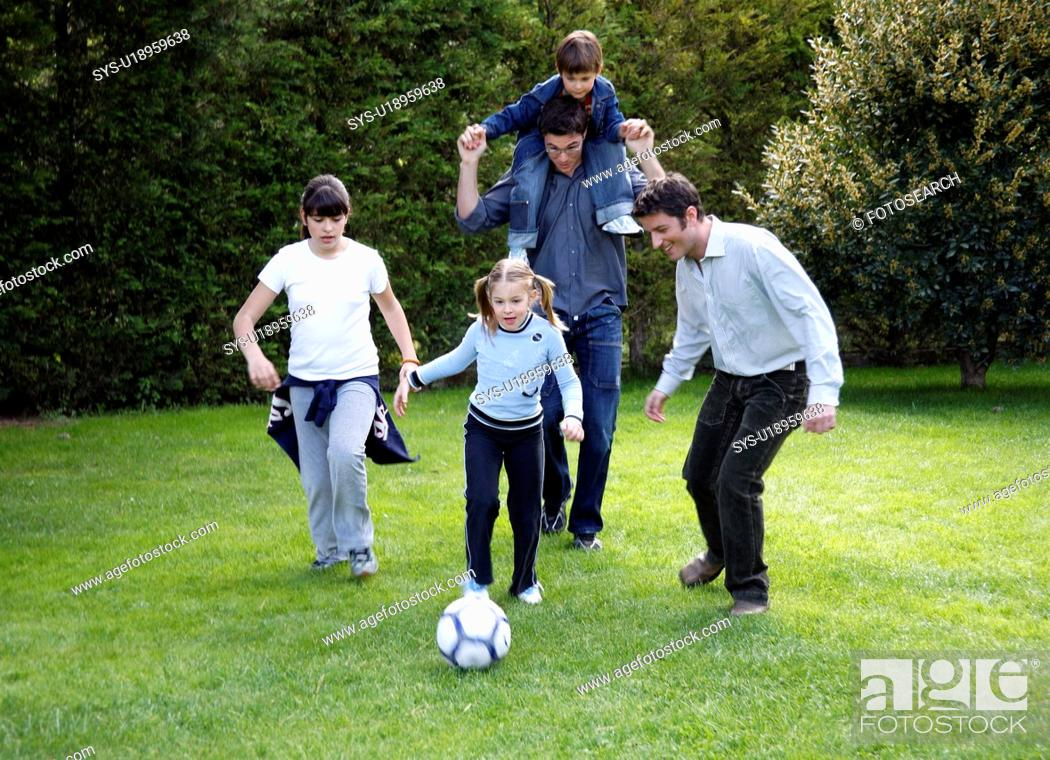 Stock Photo: Man and children playing soccer.