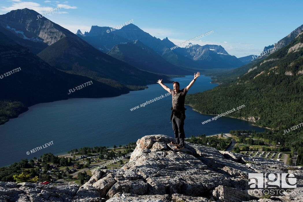 Imagen: A man stands on a rocky ridge overlooking a lake and mountains in Waterton Lakes National Park; Alberta, Canada.