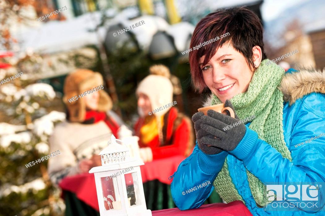Stock Photo: Austria, Salzburg, Young woman with cup, people in background.