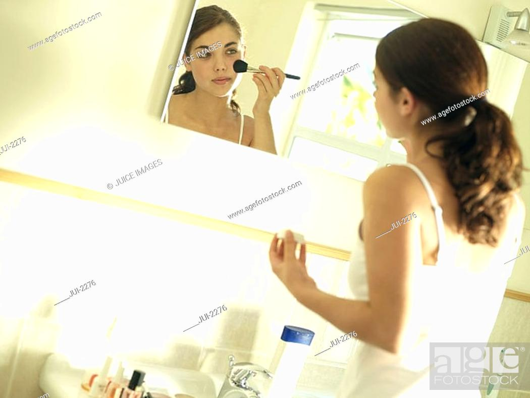 Stock Photo: Teenage girl 15-17 looking at reflection in bathroom mirror, applying make-up with brush tilt.