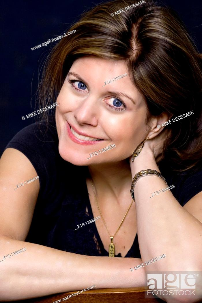 Stock Photo: Attractive woman with one arm supporting her head looks to the camera, with a warm smile.