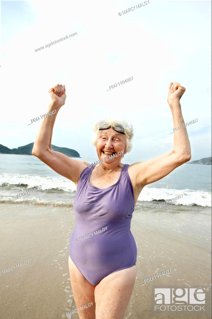 Stock Photo: Elderly woman in swimsuit and goggles on beach.
