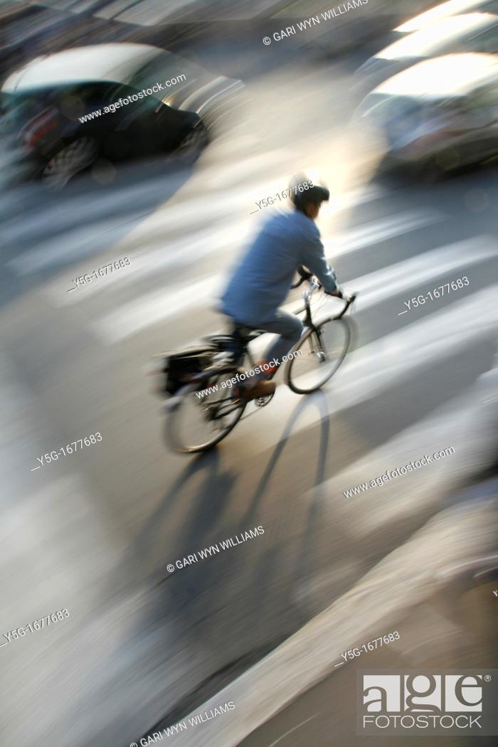 Stock Photo: person riding fast bike busy traffic city street in rome italy.