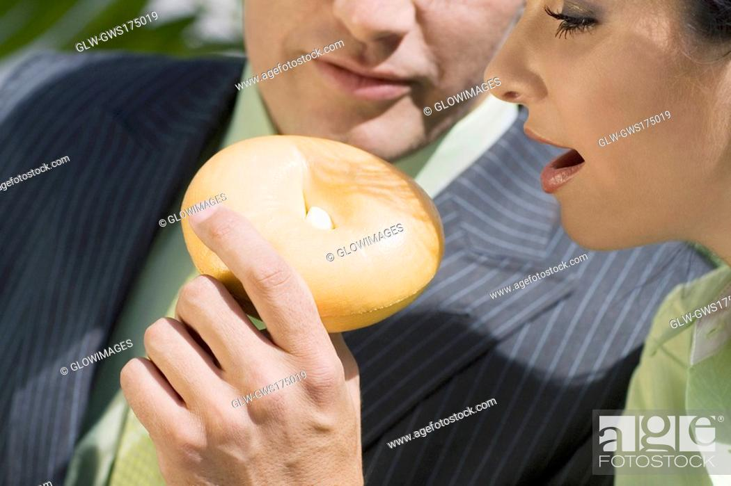 Stock Photo: Close-up of a businessman feeding donut to a businesswoman.