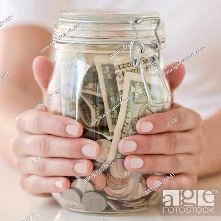 Stock Photo: Woman holding jar with money.
