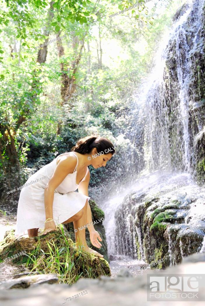Stock Photo: Young attractive brunette woman, wearing a white dress, touching the water in a beautiful natural place, with a waterfall and assorted vegetation.