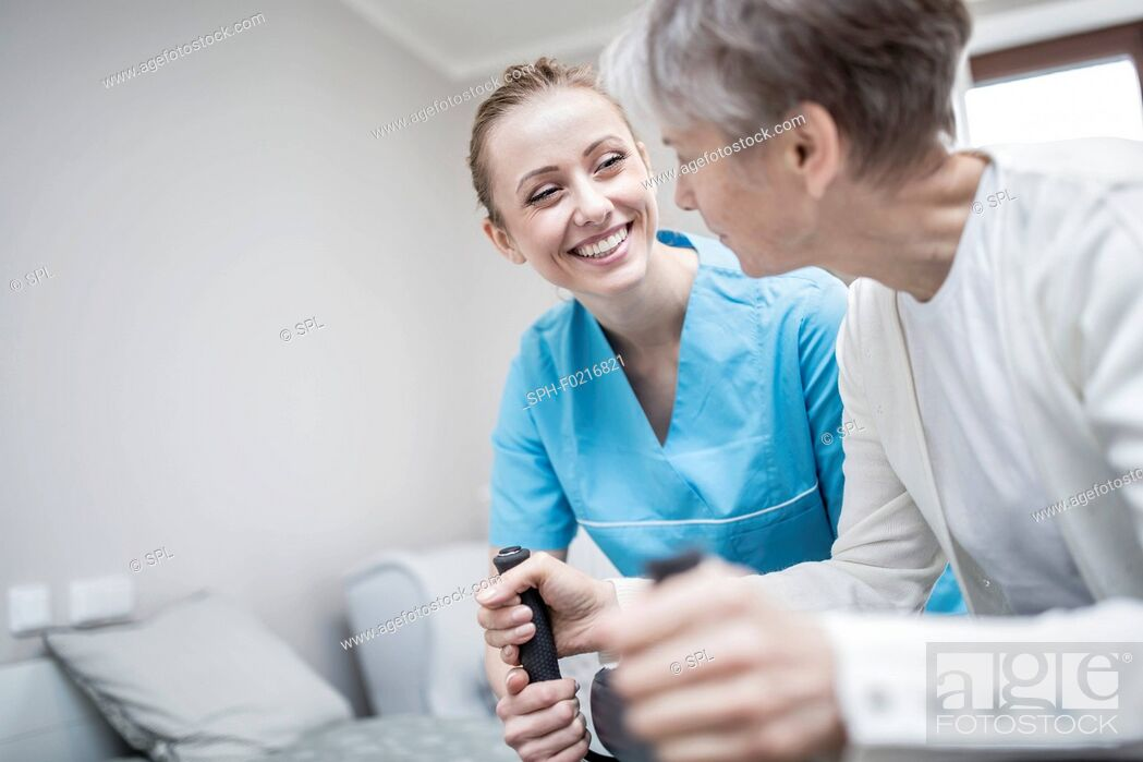 Stock Photo: Woman using rollator with carer assisting.