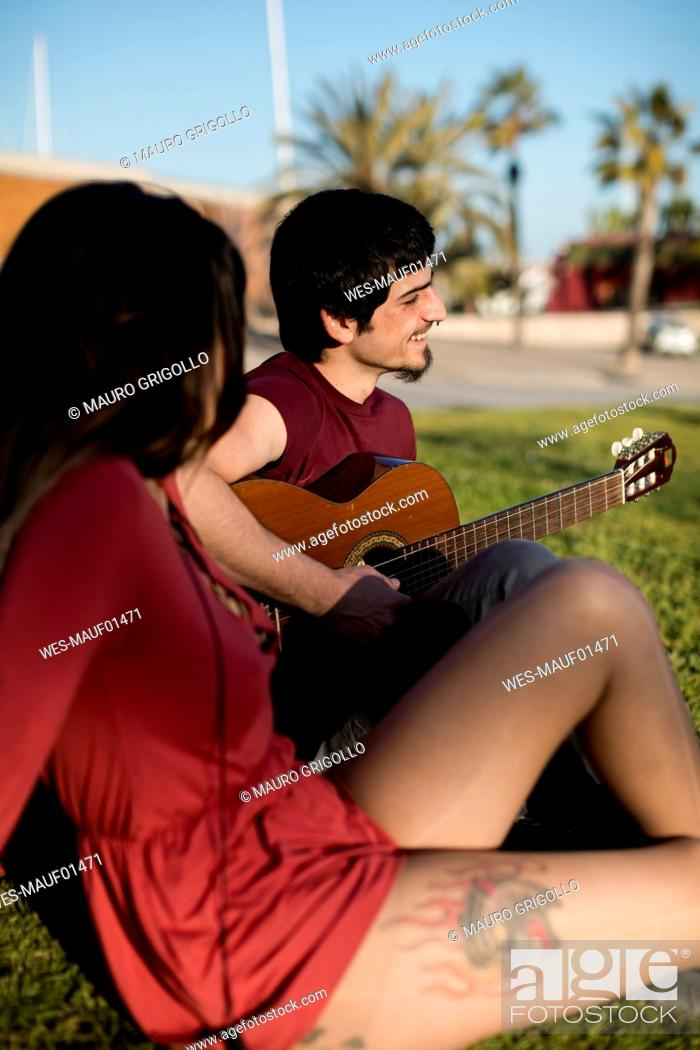 Imagen: Spain, Barcelona, smiling young man playing guitar for girlfriend sitting on a meadow.