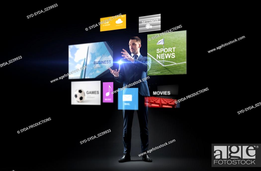 Stock Photo: businessman with applications on virtual screen.