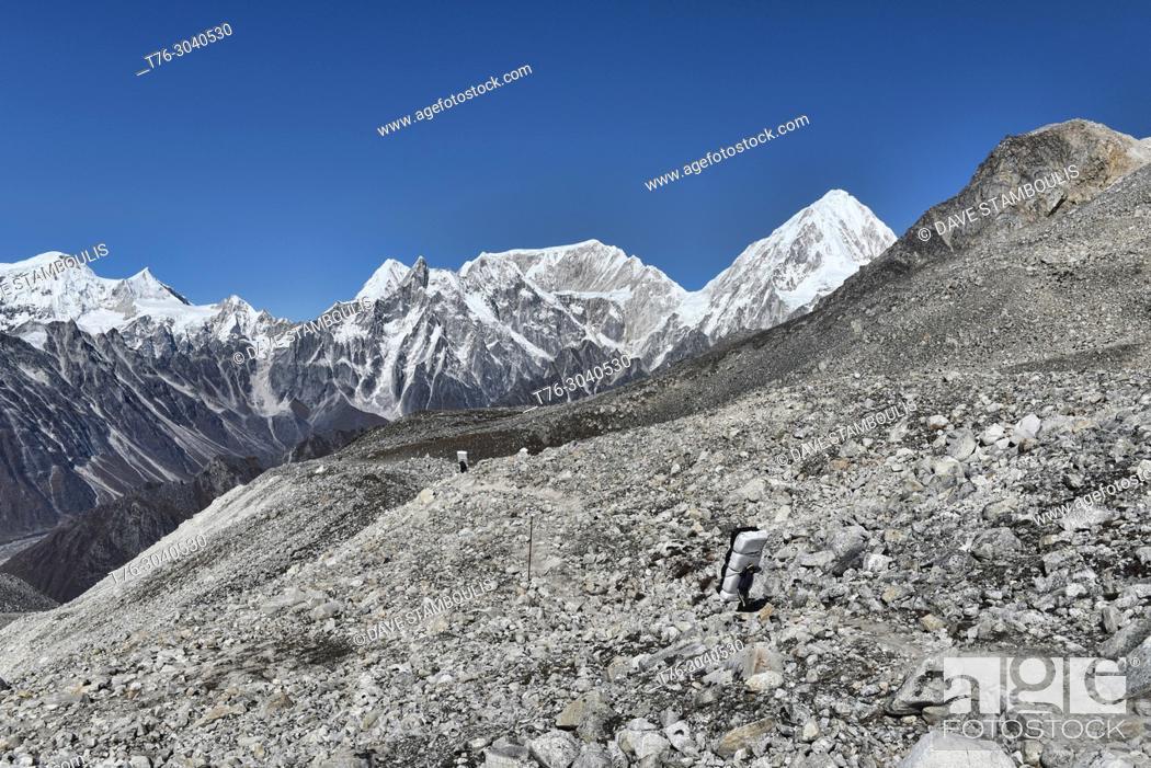 Imagen: Porters carrying huge loads up the Larkya La, Manaslu Circuit Trek, Nepal.