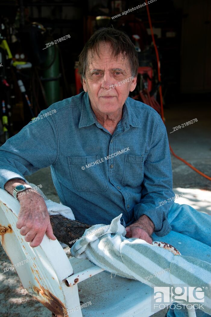 Stock Photo: An older man pauses at his workshop.