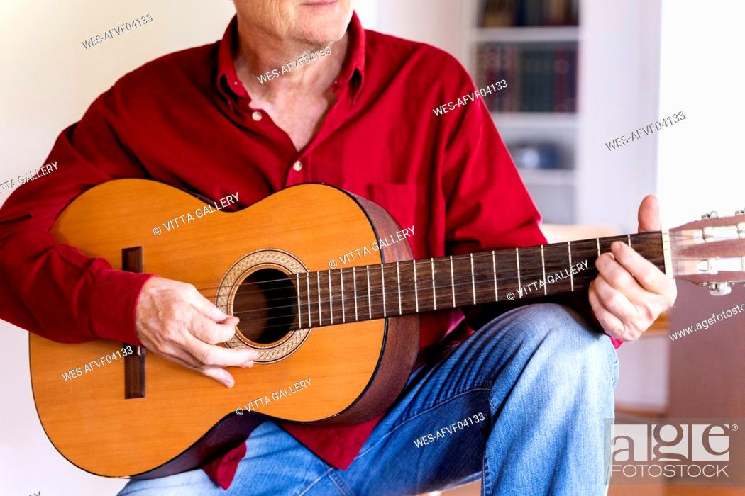 Imagen: Senior man playing guitar at home.