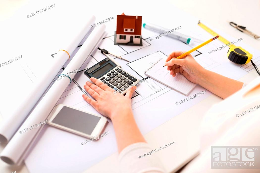Stock Photo: business, architecture, building, construction and people concept - close up of architect hand with blueprint counting on calculator.