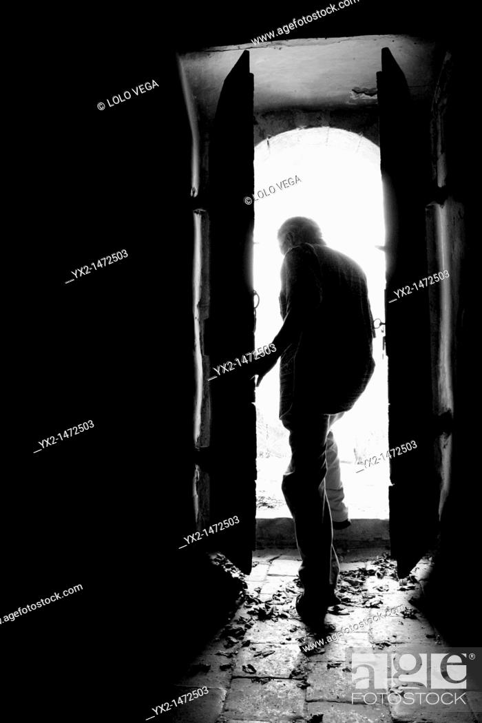 Stock Photo: Man getting out of an old door.