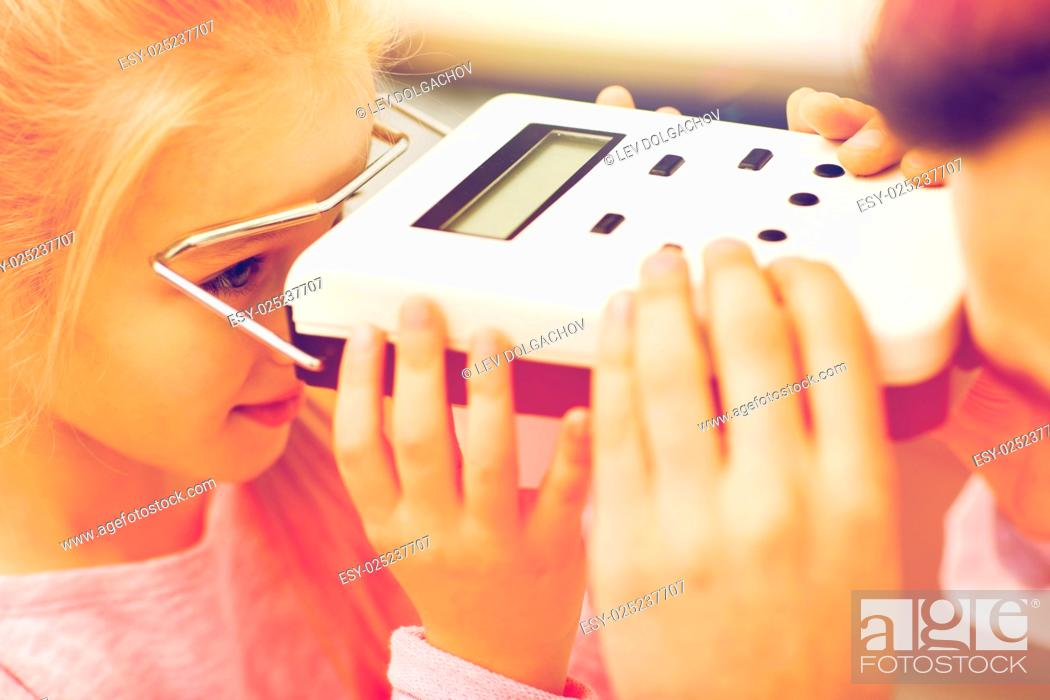 Stock Photo: health care, medicine, people, eyesight and technology concept - close up of optometrist with pupillometer checking patient intraocular pressure at eye clinic.