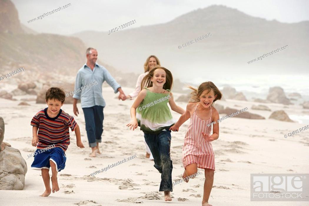 Stock Photo: Family with three children 5-6 7-9 10-12 walking on beach.